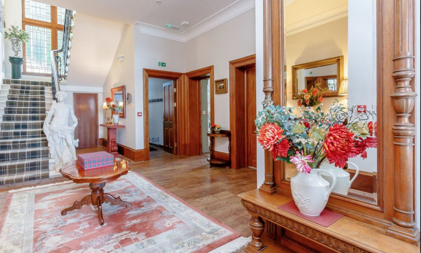Large reception all with stained glass window and staircase, wooden floors with tapestry rugs