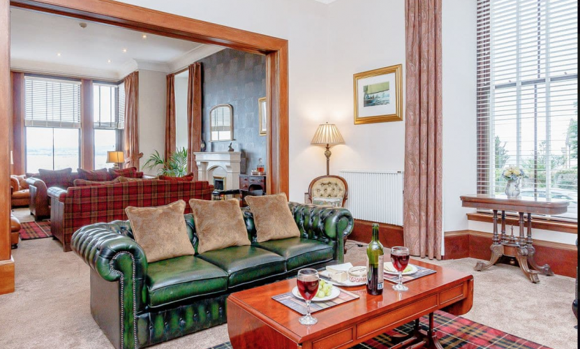 Large drawing room with leather sofas, fireplaces and huge windows overlooking the sea